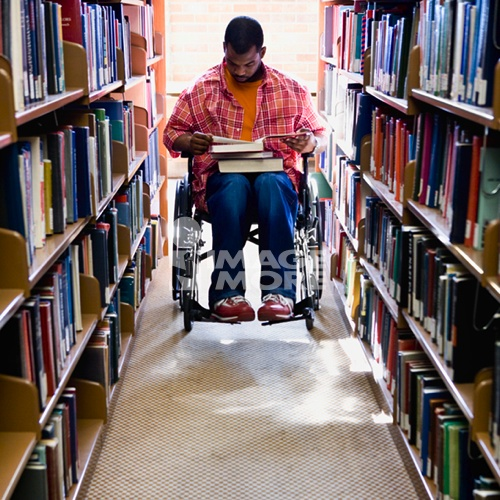African American man in wheelchair reading