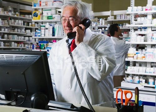 Senior Asian pharmacist talking on telephone