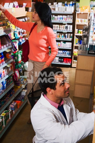 Asian woman shopping next to store clerk