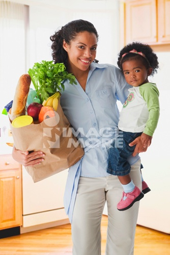 African mother holding baby and grocery bag