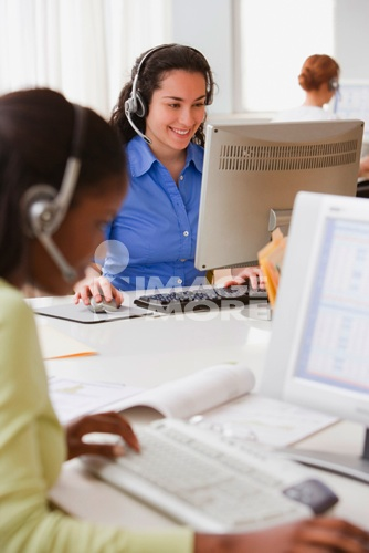 Businesswomen with headsets working at desk