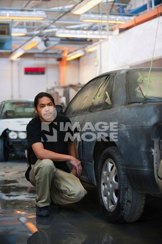 Pacific Islander worker crouching near car in auto body shop