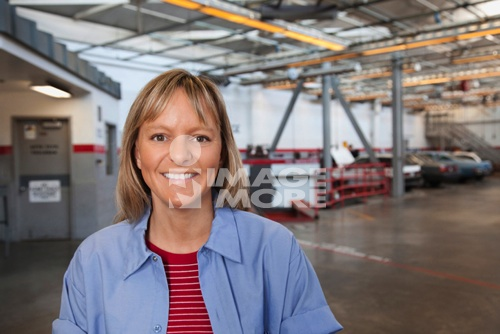 Smiling woman in auto body shop