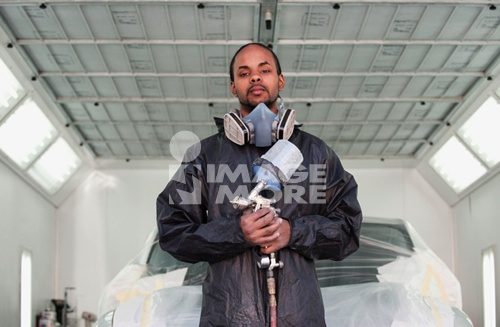 Mixed race man holding painting equipment in auto body shop