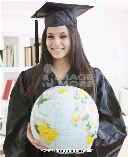 Mixed race graduate in cap and gown holding globe
