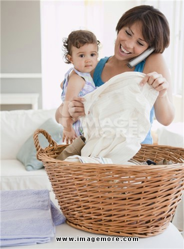 Hispanic mother holding daughter, talking on phone and doing laundry