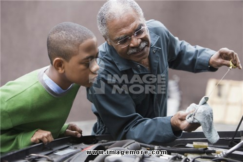 African grandfather and grandson working on car