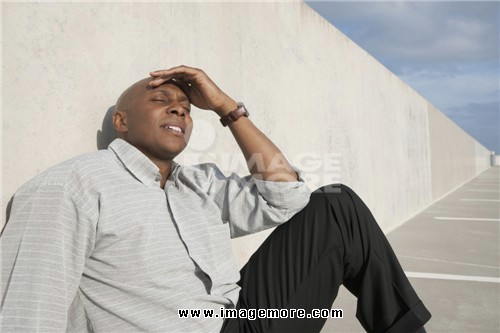 African businessman sitting on ground in parking lot