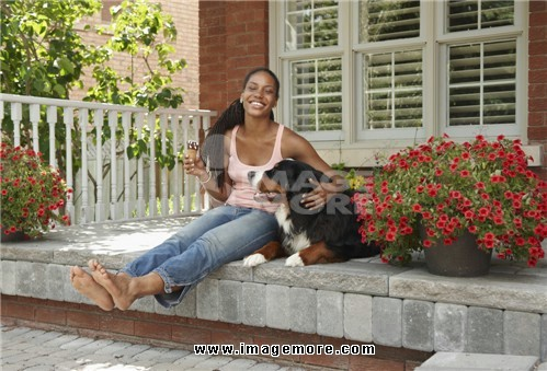 African American woman eating ice cream cone on porch with dog