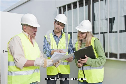 Hispanic construction workers reviewing paperwork