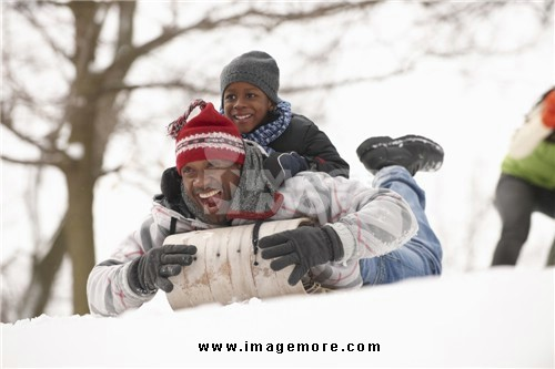 African American father and son sledding on snowy hill