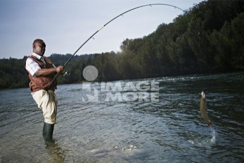 Black man catching fish in stream