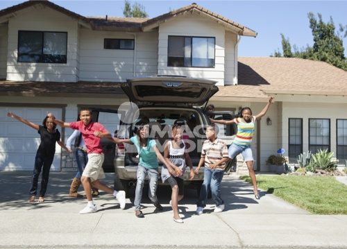Family cheering in driveway of house