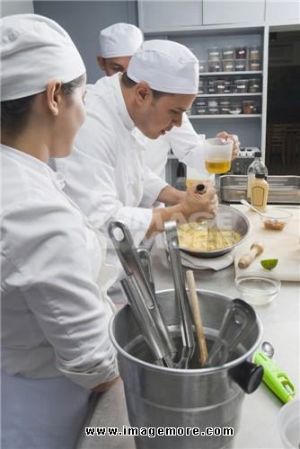Baker stirring batter in bakery kitchen