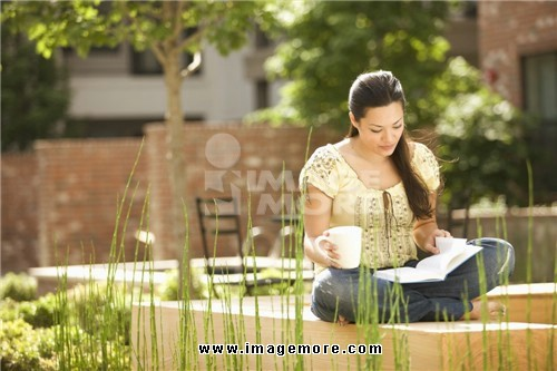Mixed race woman reading book and holding coffee cup outdoors