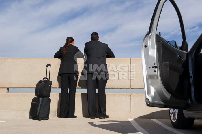 Business people leaning on railing in parking lot