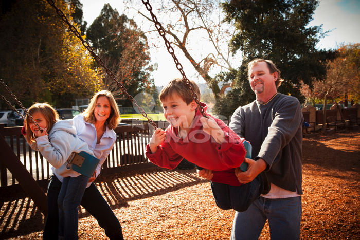 Caucasian parents swinging children on swing set