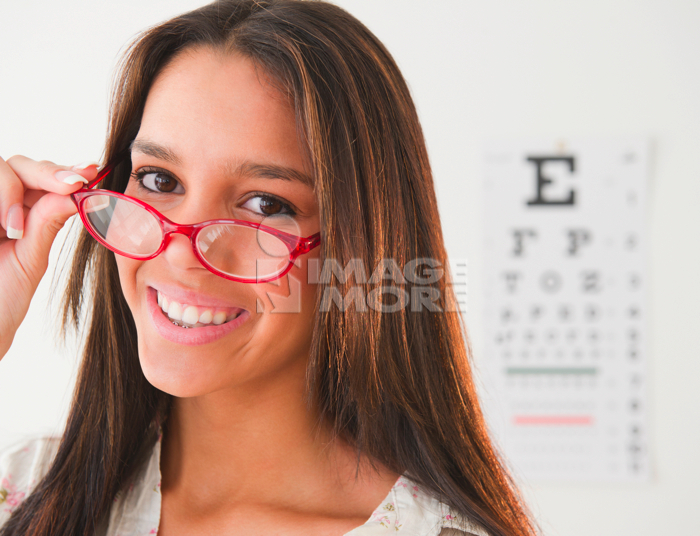 Hispanic teenage girl having eye exam