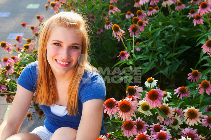 Caucasian teenager sitting near flowers