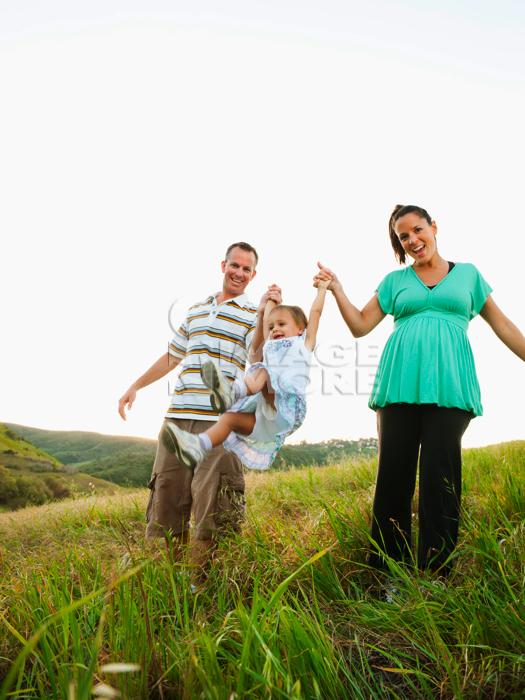 Happy parents swinging daughter in field