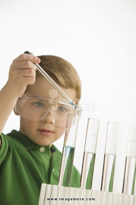 Caucasian boy putting liquid into test tubes
