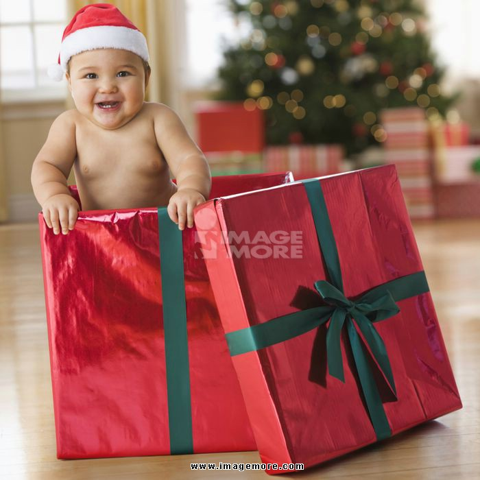 Mixed race baby boy playing in Christmas gift box