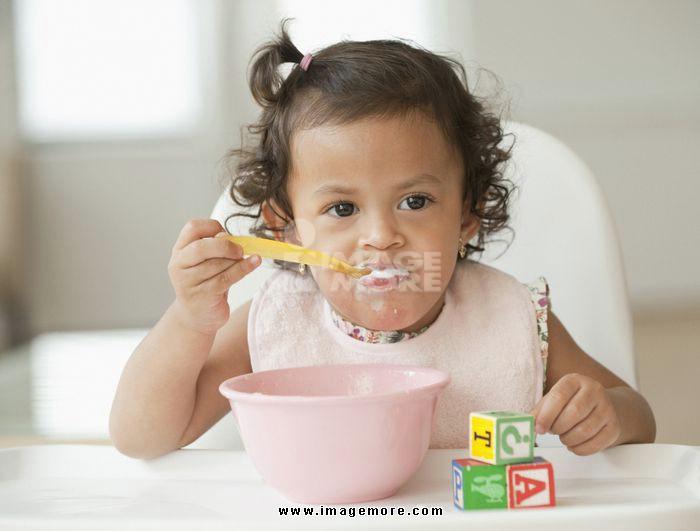 Hispanic girl eating in high chair