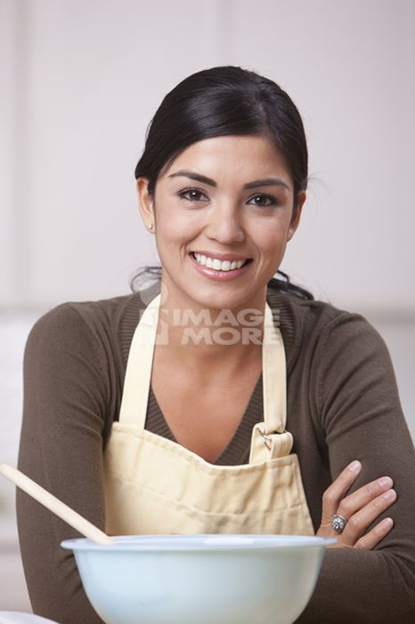 Hispanic woman in kitchen with bowl and spoon