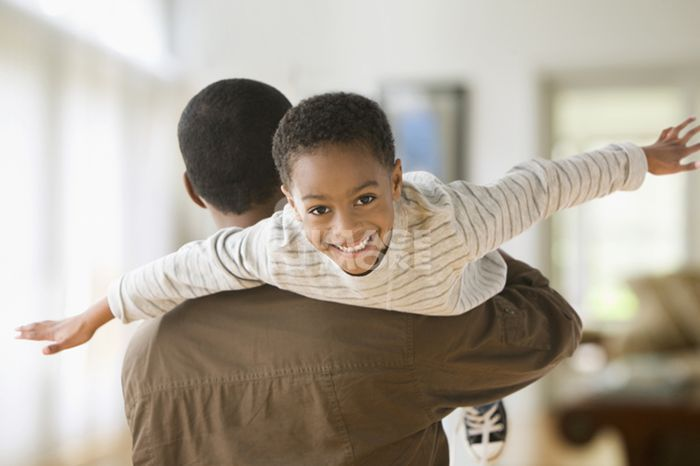 African American father carrying son on shoulders