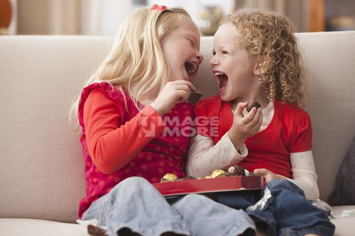 Caucasian girls eating Valentine's candy