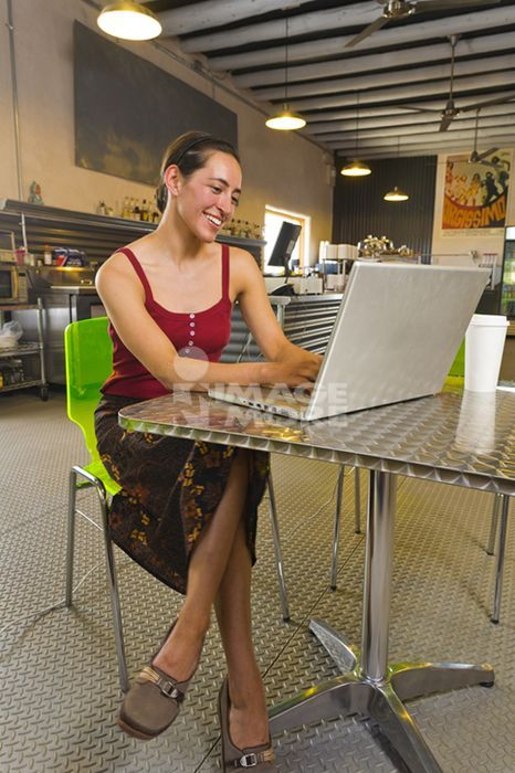 Hispanic woman using laptop in cafe