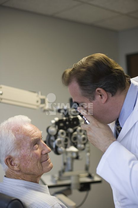 Eye doctor checking man's eyes