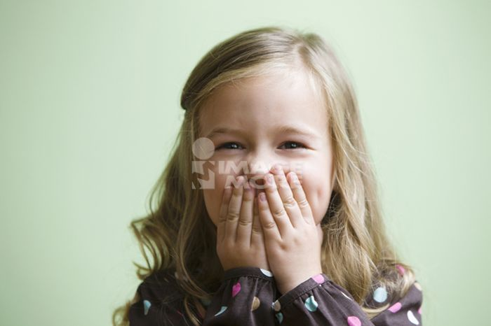 Caucasian girl covering her mouth