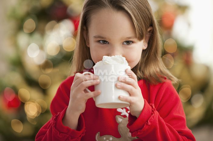 Caucasian girl drinking hot chocolate at Christmastime
