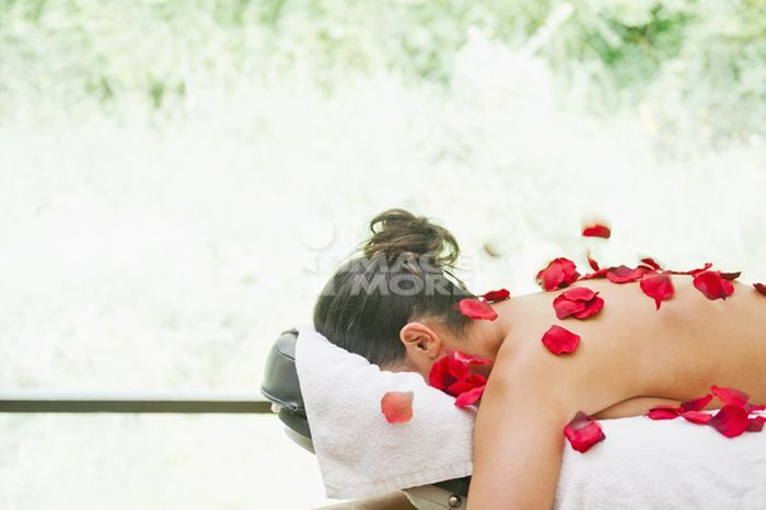 Hispanic woman laying in massage table covered in rose petals