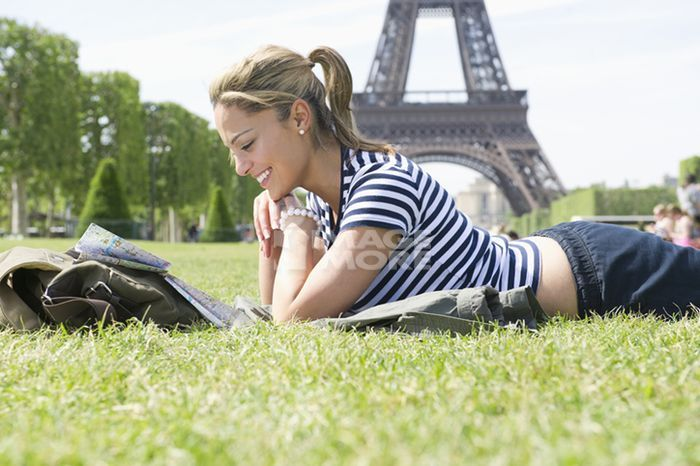 Hispanic woman looking at map in park near Eiffel Tower