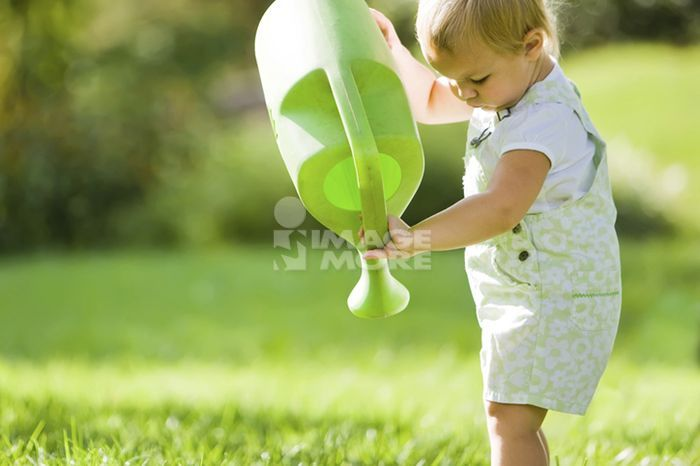 Caucasian baby lifting watering can