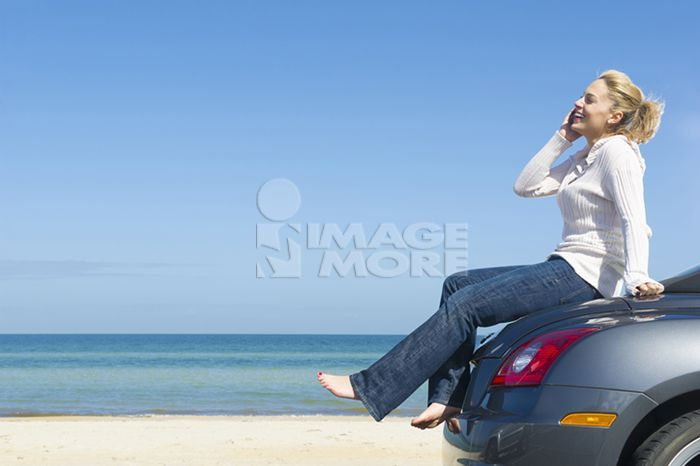Hispanic woman sitting on car using cell phone at beach