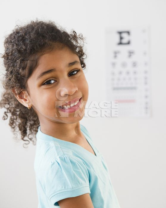 Mixed race girl having an eye exam