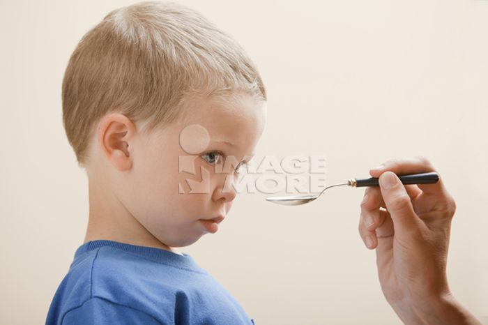 Caucasian boy taking medicine