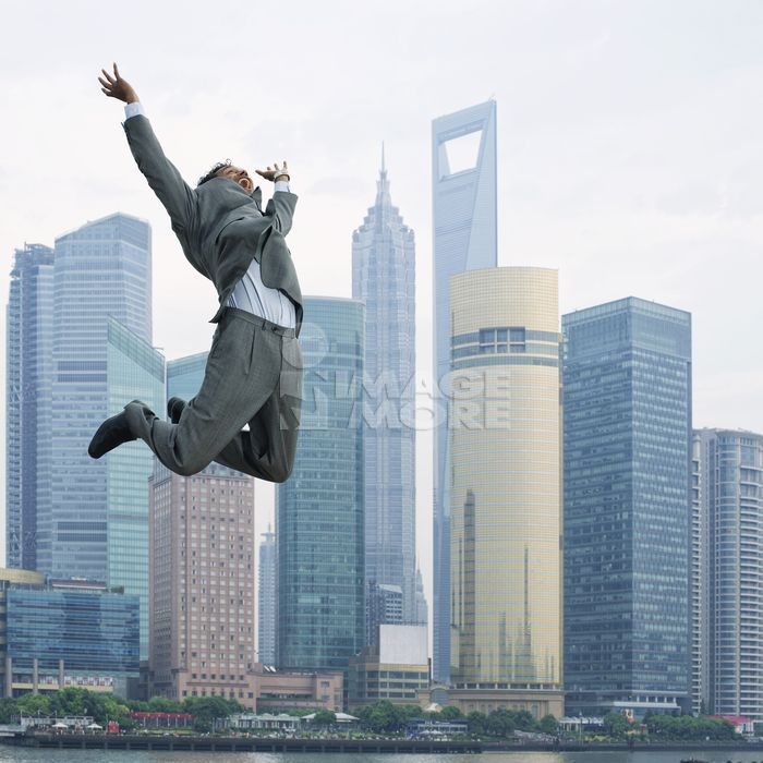 Mixed race businessman jumping in air