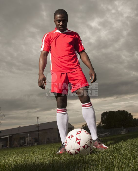 Black soccer player standing with ball