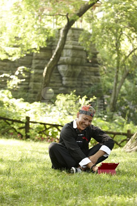 Man in traditional Asian clothing sitting in grass
