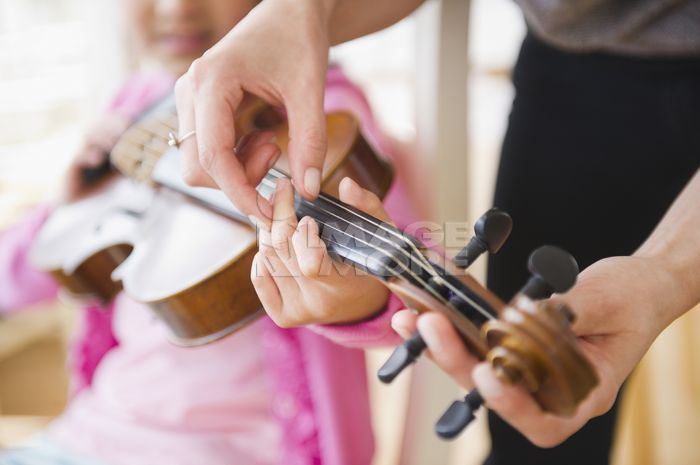 Mixed race girl learning to play violin
