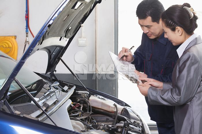Chinese mechanic talking to customer