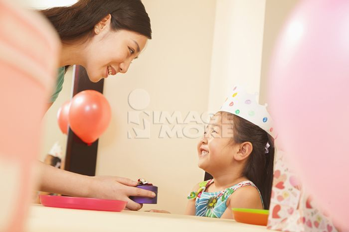 Chinese mother and daughter giving gifts at party