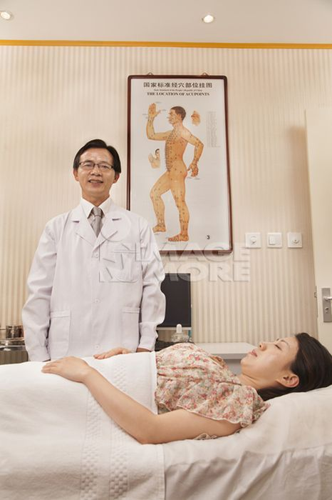 Chinese doctor using acupuncture on patient