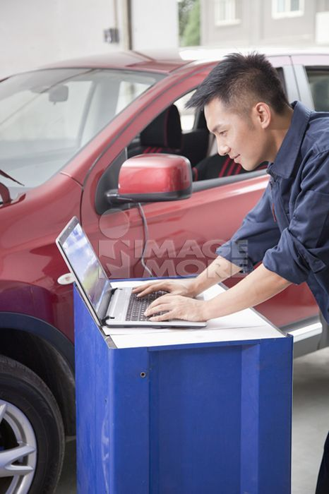 Chinese mechanic working on laptop