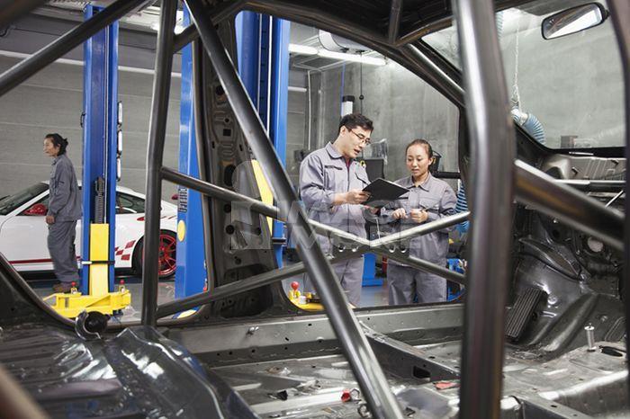 Chinese mechanics working in garage