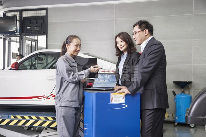 Chinese mechanic talking to customers in garage